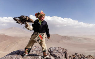 A Kazak Mongolian eagle hunter and his eagle in the Altai near to Bayan Olgii, Mongolia.