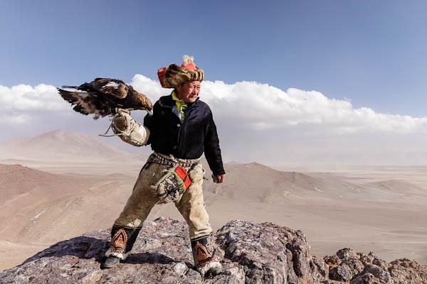 A Kazak Mongolian eagle hunter and his eagle in the Altai near to Bayan Olgii, Mongolia.